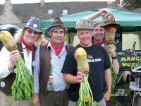 The Mangledwurzels with uberfan Mike Collier posing with some real mangold wurzels at the Sherston Village Day (31 August 2009)